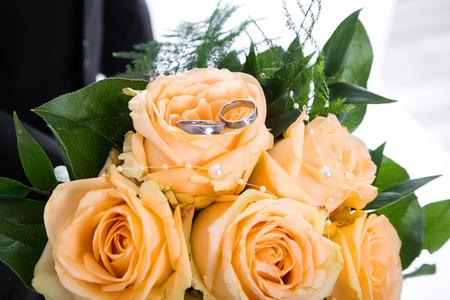 rosas naranjas: Rosas anaranjadas Ramo con anillos de boda. Foto de archivo