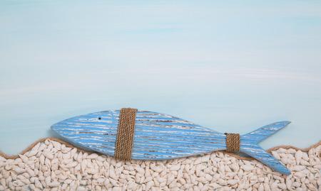 pez cristiano: Pez de madera azul sobre fondo turquesa con conchas. S�mbolo cristiano.