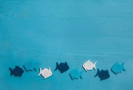 Fond bleu et turquoise en bois avec des poissons en un groupe. Idée pour le travail d'équipe ou un baptême, une communion ou la confirmation. Banque d'images - 38238722