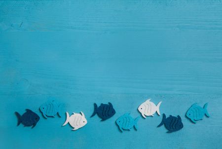 Wooden blue and turquoise background with fishes in a group. Idea for teamwork or baptism, communion or confirmation.
