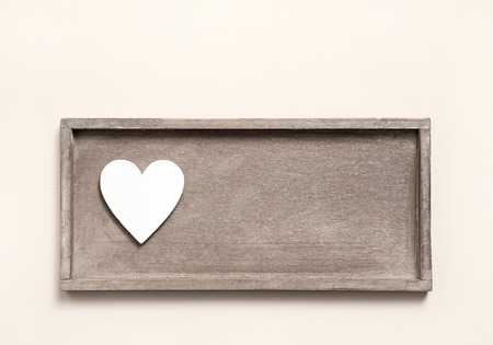 One wooden heart on a sign for a greeting card. Shabby chic style for valentines or mothers day. photo