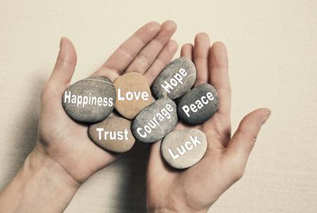 psychic: Concepto de equilibrio interno: las manos que sostienen piedras con el texto de la felicidad, el amor, la confianza, el coraje, la esperanza, la paz y la suerte. Foto de archivo