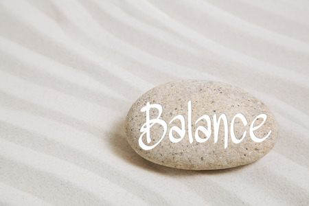 Stone in the sand with the word balance. Idea for spa and recreation concepts. Stock Photo