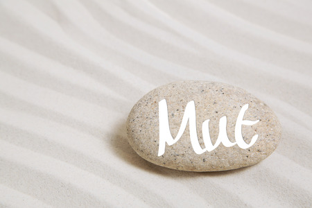 selfcontrol: Sand background with a stone and the german word for courage. Concept for start news or hope in illness.