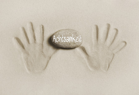 life is good: Hands print in the sand holding a stone with the german word for care or mindfulness. Concept for a good life. Stock Photo