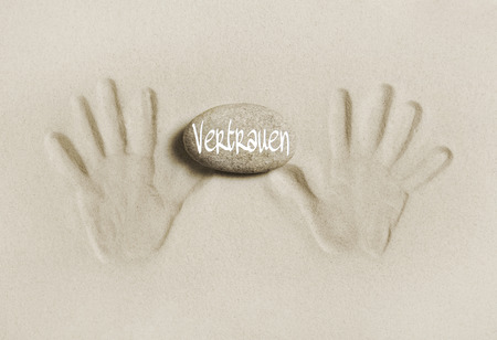 pureness: Two hands print in the sand with a stone and the word trust in german language. Concept for living together. Stock Photo