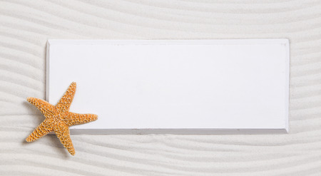 exotically: Starfish on a white sign in a sand background for summer beach items.