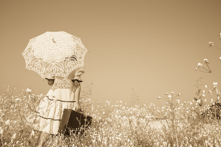 vintage landscape: Old photo in sepia color. Girl with her umbrella walking alone and searching her way. Stock Photo