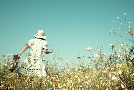 woman alone: Girl on the way to her future walking in a flowery meadow with her suitcase.