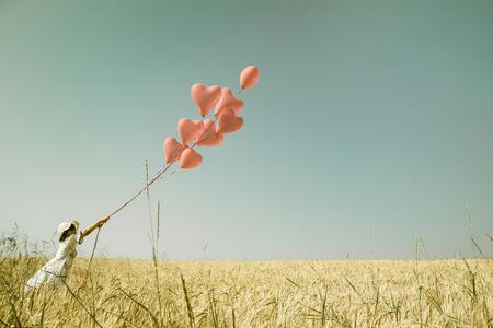 lãng mạn: cô gái lãng mạn trẻ trong summertimes với bong bóng trái tim màu đỏ đi bộ trong một lĩnh vực lúa mì.