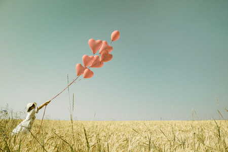 Young romantic girl in summertimes with red heart balloons walking in a field of wheat.