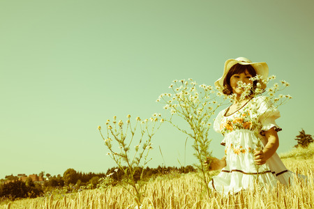 woman in field: Girl in the late summer walking through a field of wheat picking flowers. Stock Photo