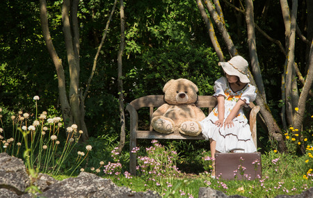 humorously: Little girl with her teddy bear sitting on a wooden bench in the garden talking together.