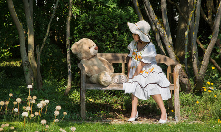 Little girl with her teddy bear sitting on a wooden bench in the garden talking together.