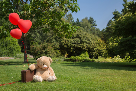 Sad teddy bear with red hearts balloons. Concept for missing you or forgive me. Stock Photo