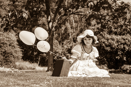 lonesomeness: Sad and alone. Young girl sitting with her bag unhappy in the park. Stock Photo