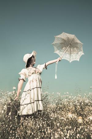 femme romantique: Bonne jeune fille en robe de style campagnard tendant la main avec parasol dans le ciel. Contexte de charme shabby chic. Banque d'images
