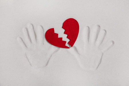 lovesickness: Broken red heart with hands. Stock Photo