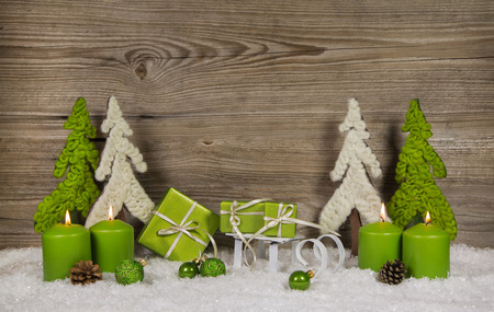 christmas trees: Four green burning christmas candles with presents and trees on wooden background for a card.
