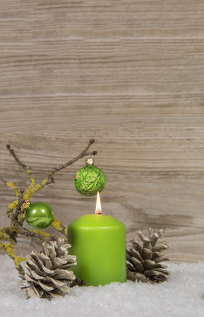 background green: One burning christmas candle on an empty wooden background with snow and other decoration.