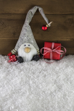 gnome: Funny gnome on wooden background with red christmas gifts. Stock Photo