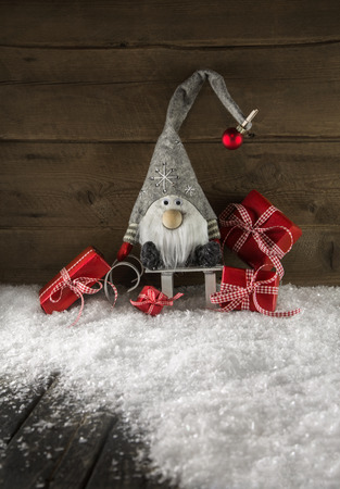 Funny gnome on wooden background with red christmas gifts. Stock Photo
