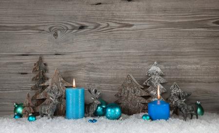 candela: Fondo rustico di Natale in legno con le candele due blu turchese, cervi e la neve per le decorazioni. Archivio Fotografico
