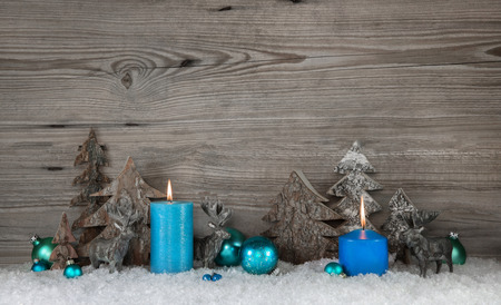 Rustic wooden christmas background with two blue turquoise candles, deers and snow for decorations. Stockfoto