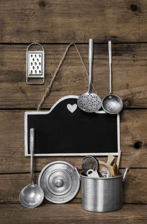 vintage kitchen: Wooden vintage kitchen background with old kitchenware, blackboard and spoons for cooking.