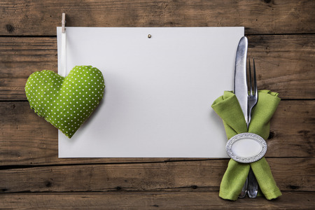 cutlery: Menu card with a green heart and white dots plus cutlery and napkin for a background. Stock Photo