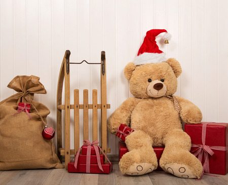humorously: Teddy bear as a santa with an old wooden sleigh, jute sack and red christmas presents. Stock Photo