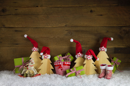 xmas background: Red, green, yellow and brown xmas background with gifts rocking horse and santa hats on wood with snow.