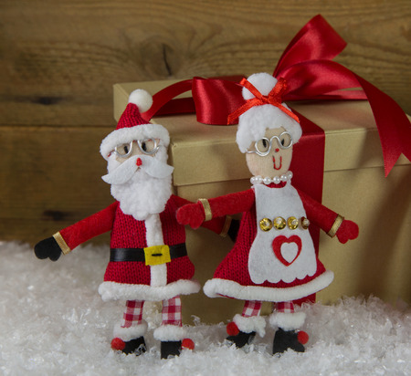 humorously: Santa couple. Handmade of felt and fabrics with a big red gift in the background. Stock Photo