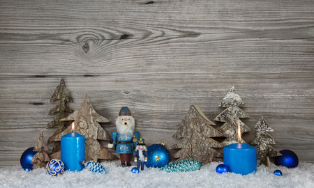 christmas candles: Wooden xmas background in grey with blue turquoise nutcrackers, snow and candles in country style decoration.