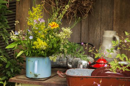 Vieux anciens ustensiles de cuisine avec un bouquet de fleurs dans le jardin.