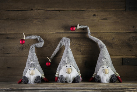 humorously: Three handmade imps on wooden background wearing santa hats for christmas decoration.