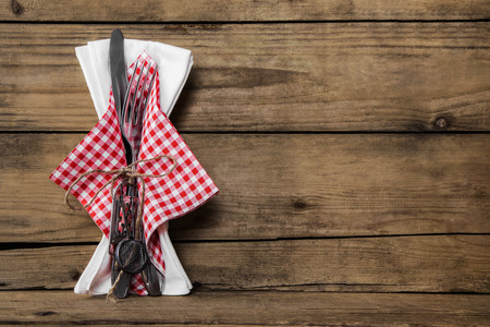 Fork and knife set with red white checked napkin on old rustic wooden background for a menu card. Foto de archivo