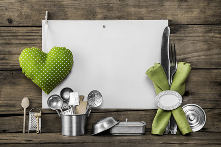 Menu card with old kitchen utensils, white placard, apple green doted heart, equipment and pots on an old nostalgic background.
