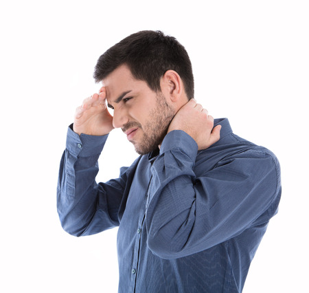 head and  back: Isolated man in blue shirt with pains in the neck over white.