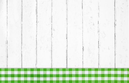 Old lime green white checked wooden background with fabrics on the frame.