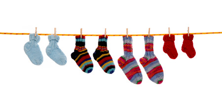 hanging: Four pairs of isolated handmade red and blue wool socks hanging on a rope. Stock Photo