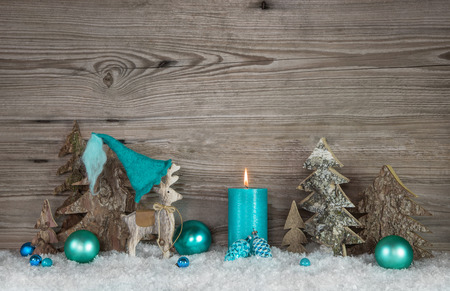 christmas atmosphere: Country style greeting card for christmas with candle and elk in turquoise and brown colors.