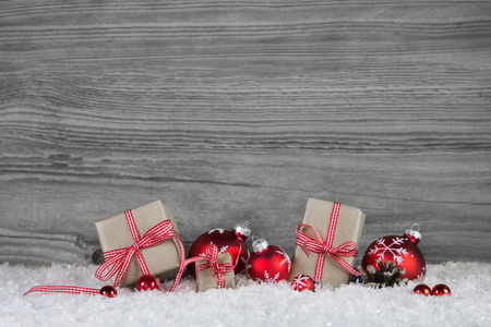 Christmas gift boxes wrapped in paper decorated with red balls on grey wooden background.