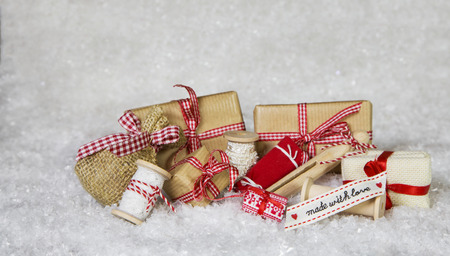sewing box: Homemade christmas presents wrapped in paper with ribbon and bows on white and red background.