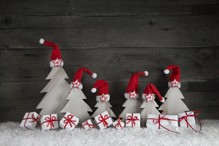 Funny christmas trees with santa hats and presents on wooden background with red ribbon and snow for decoration.