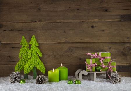 Two apple green burning candles for advent. Christmas decoration with gifts on wooden old brown country background.