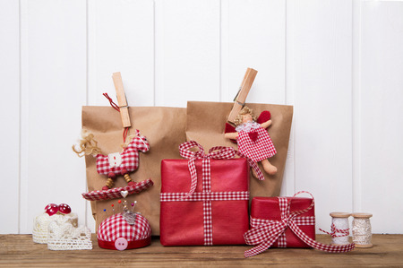 country christmas: Christmas gift boxes wripped in paper bags with red white checked ribbon, angel, rocking horse and sewing supplies.