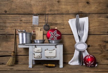 Old christmas decoration with cutlery, pots and other kitchen equipment on old wooden brown background.