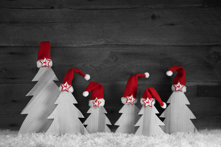 handmade: Handmade christmas trees with red santa hats on wooden old background for decoration.
