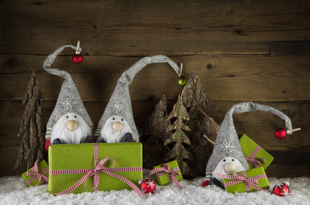 Witty christmas decoration with santa and apple green and red presents on wooden snowy background.